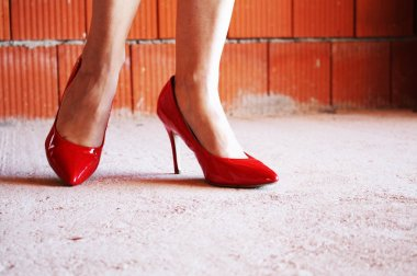 woman legs with red heel shoes in an unfinished house