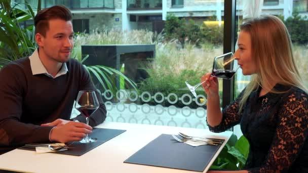 Muž a žena (mladá a atraktivní) sedět u stolu v restauraci a nápoje víno, namluví a žena poslouchá