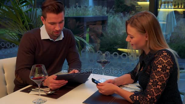 A man and a woman (both young and attractive) sit at a table in a restaurant, he holds a tablet, she holds a smartphone, he explains something about the devices