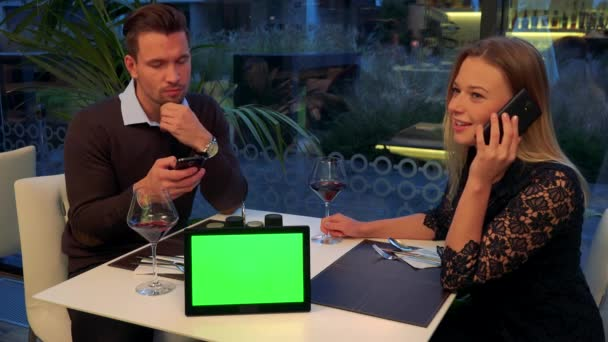 A man and a woman sits at a table in a restaurant, he texts and she talks on her smartphone, a tablet with a green screen on a table