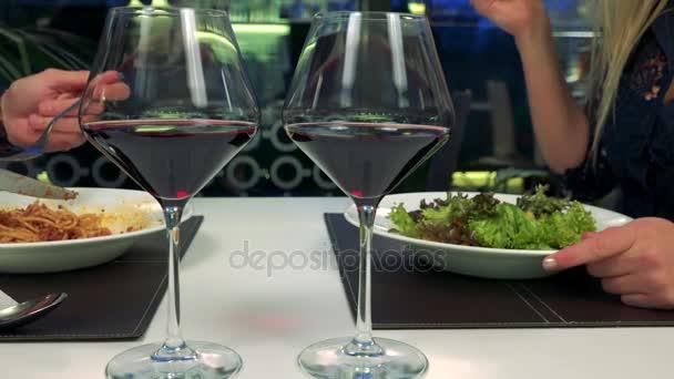 Muž a žena jíst u stolu v restauraci, dvě sklenky vína v popředí