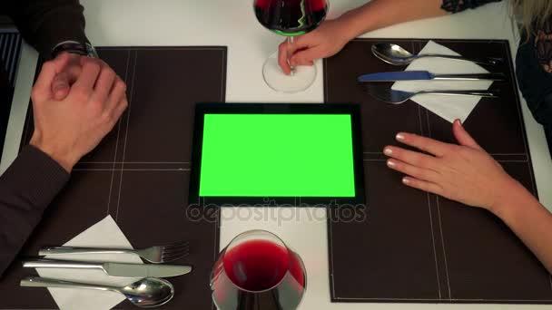 Egy férfi és egy nő ül egy asztalnál (csak láttam), a tabletta egy zöld képernyő közöttük, az ember megmagyarázza valami róla
