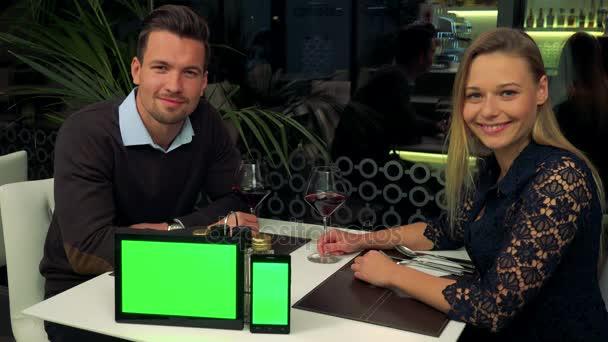 Muž a žena (mladá a atraktivní) sedět u stolu v restauraci a úsměv do kamery, tabletu a smartphonu s zelené obrazovky na stůl