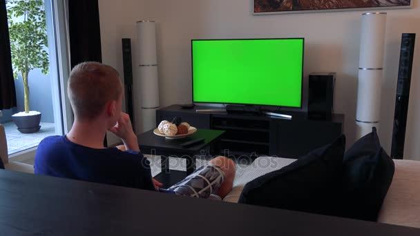 Muž se dívá na televizi s zeleným plátnem v útulném obývacím pokoji, nakonec vypadá daleko