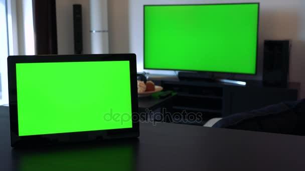 Tablet na stole v horizontální poloze - Tv v pozadí, obě mají zelené obrazovky