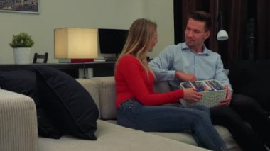 A man and a woman (both young and attractive) sit on a couch, the man shows her DVDs