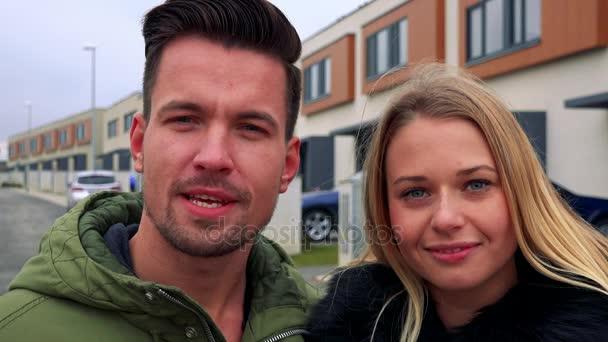 Muž a žena (mladá a atraktivní) mluvit s fotoaparátem a úsměv, čtvrť v pozadí - detailní
