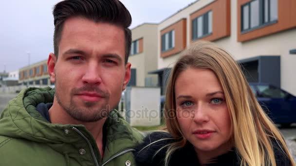 Mladá, atraktivní pár stojí na ulici a hledí do kamery - detailní