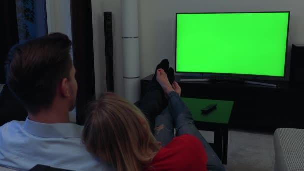 Pár (na zádech jejich hlavy k fotoaparátu) se dívá na televizi s zeleným plátnem v útulném obývacím pokoji, nohy na stůl