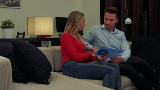 A young, attractive couple on a couch in a cozy living room discuss a DVD they hold