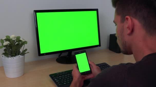 Muž hodinky v zapne svůj smartphone a počítačový displej, obě zelená obrazovka