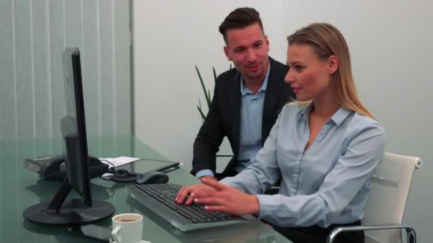 Two office staff members sit at a desk, the woman works on a computer, the man beside her pretends to choke her, they laugh