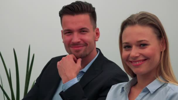 Formally clothed man and woman (both young and attractive) smile at the camera, a white wall in the background
