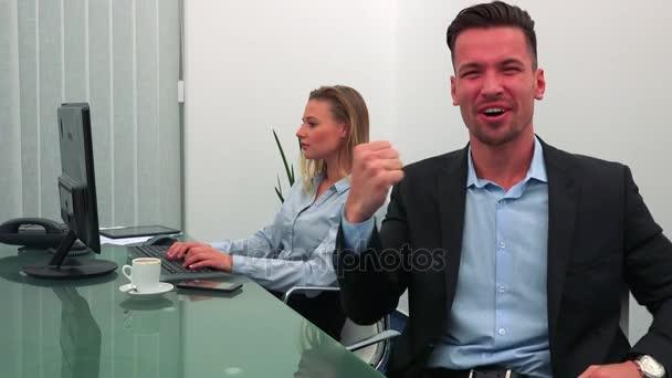 Ein junger, gutaussehender Mann feiert und lächelt in einem Büro in die Kamera, sein Kollege arbeitet im Hintergrund am Computer