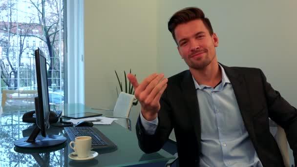 Mladý, pohledný muž sedí za stolem v kanceláři, usměje se na kameru a ukazuje gesto Pozvánka
