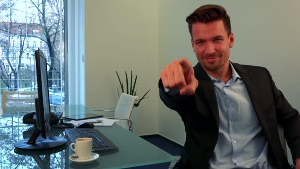 Mladý, pohledný muž usmívá se a ukazuje na kameru v kanceláři