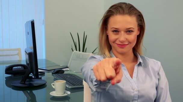 Mladá, atraktivní žena sedí u stolu v kanceláři, úsměvy a body na kameru