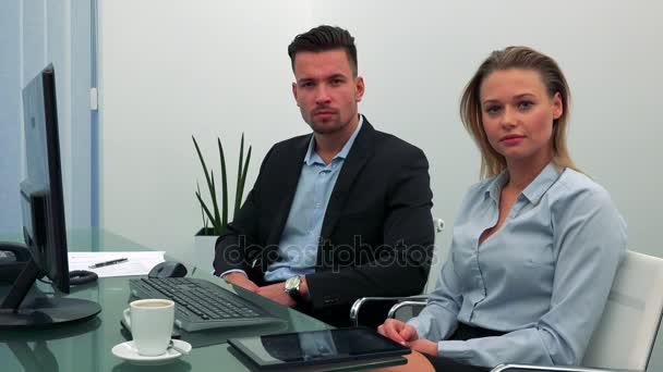 Muž a žena (mladá a atraktivní) sedět za stolem v kanceláři a podívat se na kameru