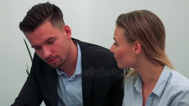Muž a žena (mladá a atraktivní) sedět a dívat se dolů na stůl, který je mimo kameru a diskuse