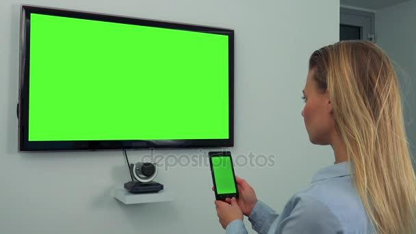 Žena vypadá v zatáčkách na zelené televizní obrazovky a smartphone s zeleným plátnem