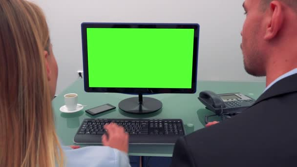 A man and a woman sit in front of a computer with a green screen in an office, he talks and she types