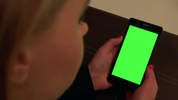 Žena sedí u stolu v restauraci a dívá na smartphone s zeleným plátnem