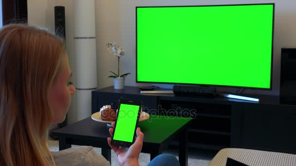 A blonde woman sits on a couch in a living room and looks in turns at a TV and a smartphone (both green screen)