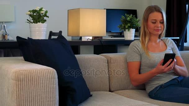 Egy fiatal, gyönyörű nő ül a nappaliban a kanapén, és úgy néz ki, felváltva a smartphone és TV-vel, ami ki van kapcsolva a kamera