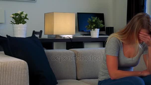 Mladá, krásná žena sedí na gauči v obývacím pokoji, pokrývá její tvář s její dlaně a zobrazí zklamání