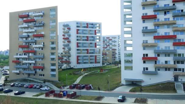 Barevné bytových domů v projektu bydlení, silnice s zaparkovaných aut v popředí, na jasné obloze na pozadí - pohled shora