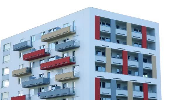 die Spitze eines bunten Wohnhauses in einem städtischen Gebiet, der helle Himmel im Hintergrund