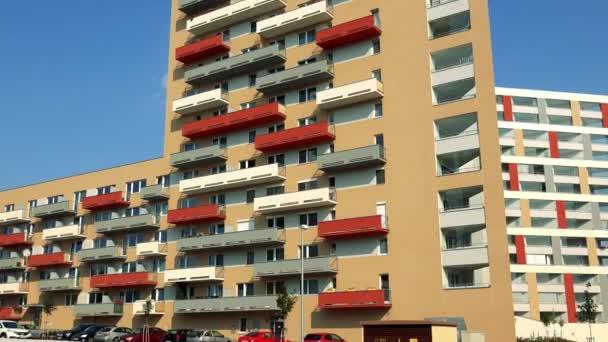 ein beiges Mehrfamilienhaus mit bunten (roten, grauen, gelben) Balkonen im Stadtgebiet, darunter ein Parkplatz, blauer Himmel und ein weiteres Mehrfamilienhaus im Hintergrund, im Vordergrund Gras