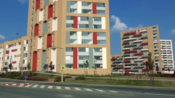 Egy városi terület, a kék ég, a háttérben, egy út az előtérben színes lakóházak