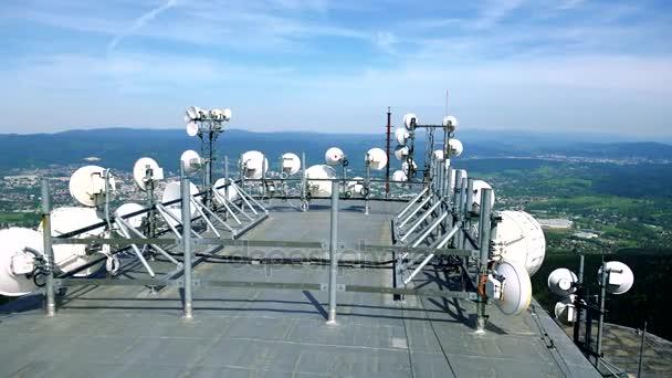Bianche antenne paraboliche sul tetto di un edificio, una città, una foresta ed il cielo blu sullo sfondo