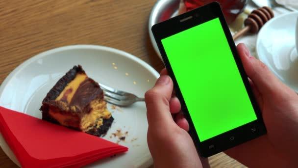 muž drží smartphone s zeleným plátnem