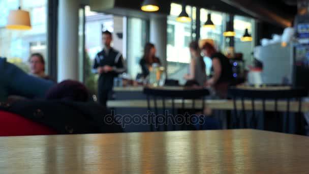 Rozmazaný přeplněné interiér kavárny z tabulky