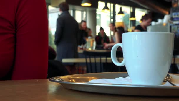 A woman sits at a table with a cup in a cafe