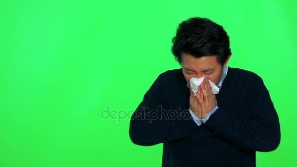 Mann ist krank und bläst seine Nase in ein Papiertaschentuch