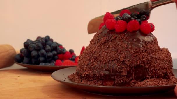 Egy nő darabok egy csokoládé torta málna és áfonyák