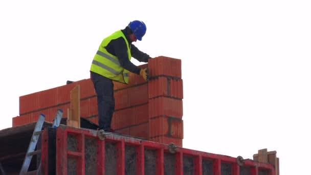 dělník staví zeď na stavbu budovy