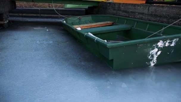 Boot an einem Kai auf einem zugefrorenen Fluss geparkt