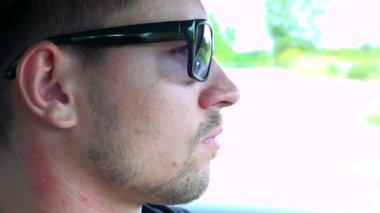 Man drives a car with sunglasses on the road