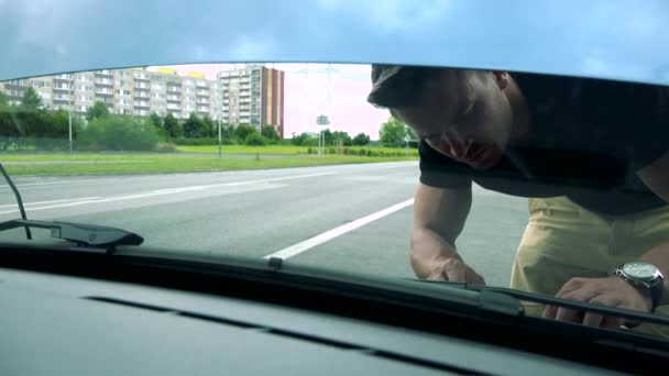 man looks and checks engine in car