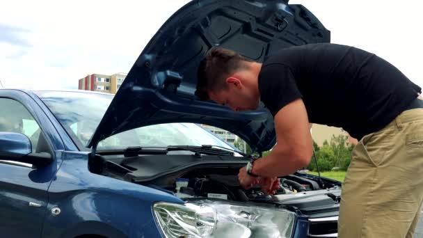 Mann schaut und kontrolliert Motor im Auto