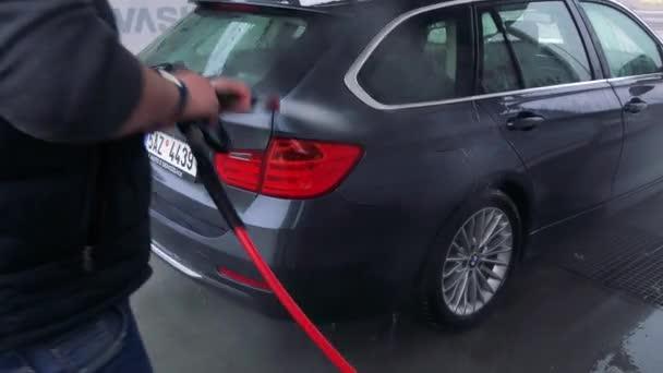 Muž omývá zadní část svého vozu s hadicí