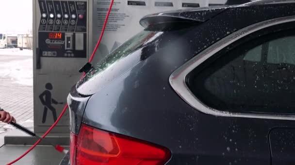 Muž omývá zadní části auta s hadicí