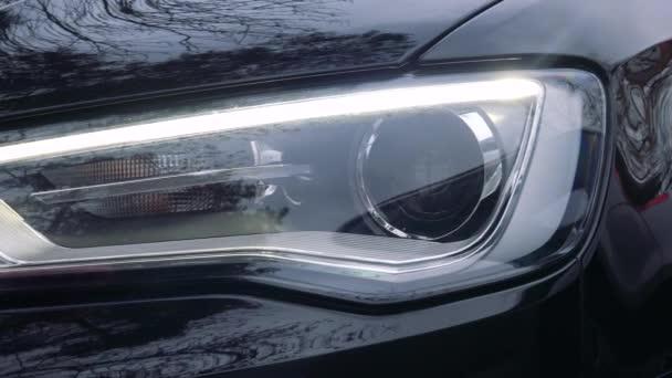 Detailní záběr na reflektor tmavě šedé auto