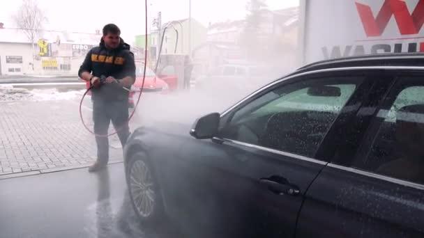 Muž omývá přední části auta s hadicí