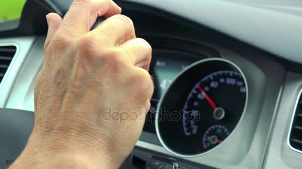 Senior man drives a car - closeup of hand on the steering wheel and speedometer