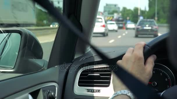 Senior man drives a car - closeup of hand on the steering wheel and speedometer - shot over seat belt - other cars on the road in the background